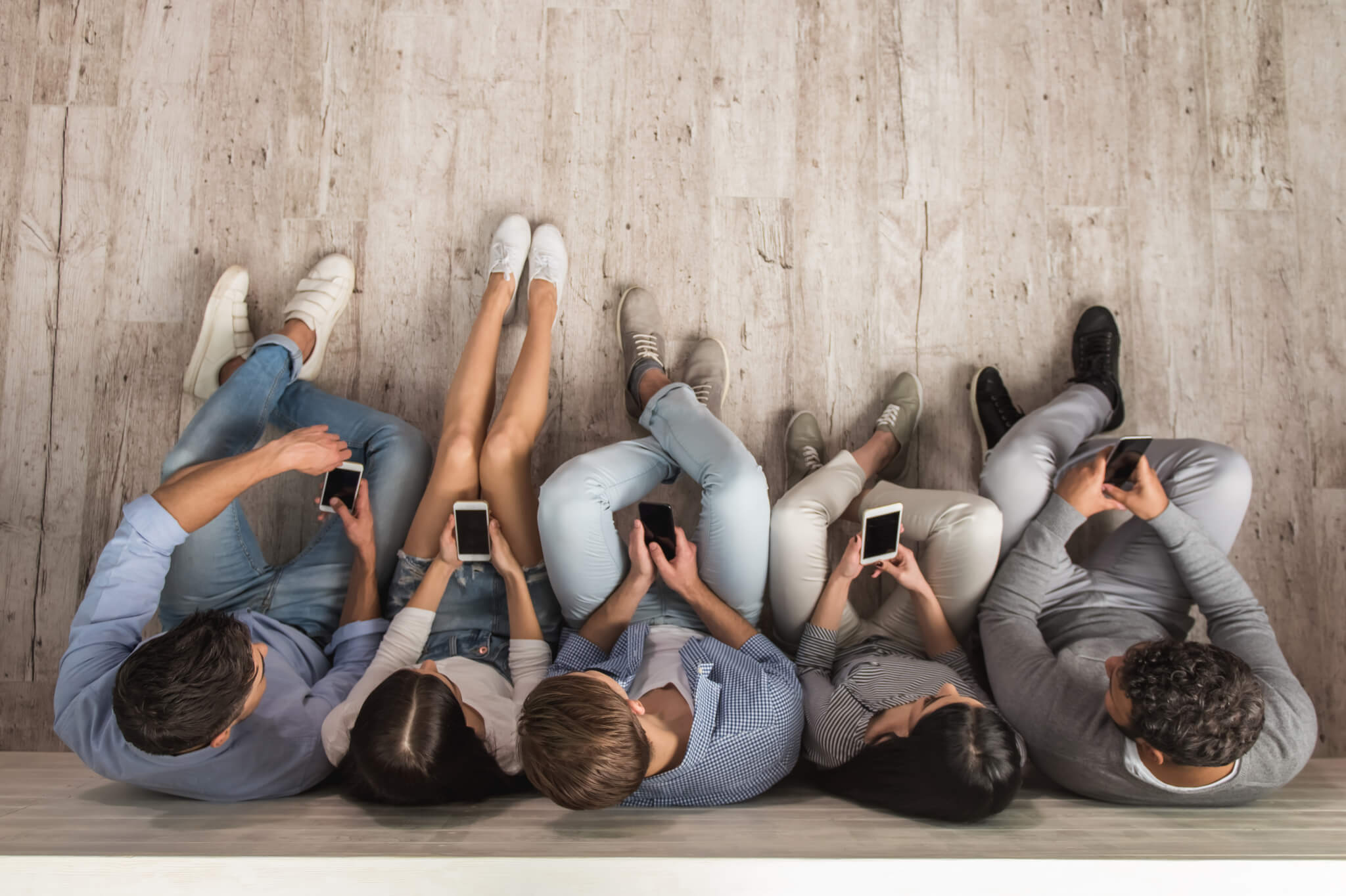 stock-photo-top-view-of-beautiful-young-people-in-casual-clothes-using-smartphones-while-sitting-together-on-588275837